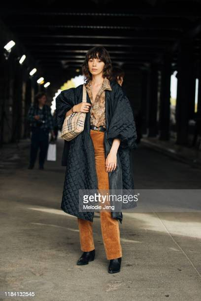 Model Vitalina Burton wears a black down jacket python print top brown suede pants black boots and Burberry check bag after the Y/Project show show...