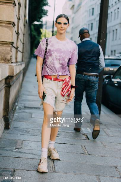 Model Vittoria Cerettti wears a purple tie-dye t-shirt, red scarf as a belt, white fringe cutoff shorts, white socks, and white Gucci sneakers after...