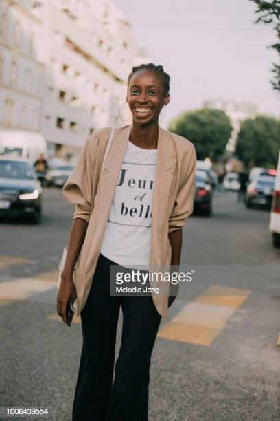 Model Viviane Oliveira wears hoop earrings and a tan jacket after the Alyx show during Paris Fashion Week Mens Spring/Summer 2019 on June 24 2018 in...