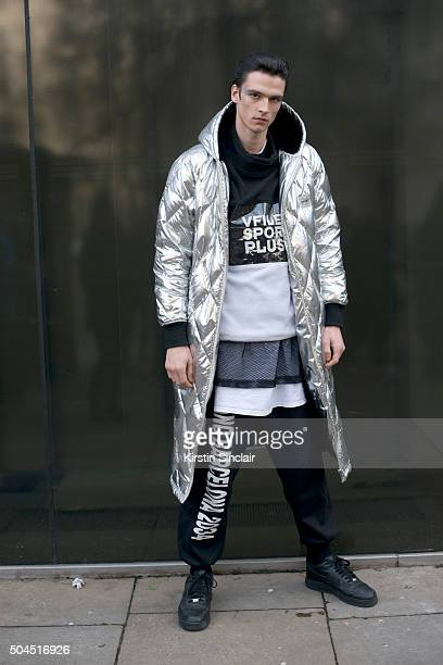 Model Vlad B wears a Vfiles coat WIA tracksuit trousers and vest and Nike trainers on day 3 of London Collections Men on Januay 10 2016 in London...