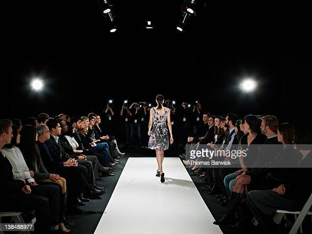 model walking down catwalk during fashion show - catwalk stock pictures, royalty-free photos & images