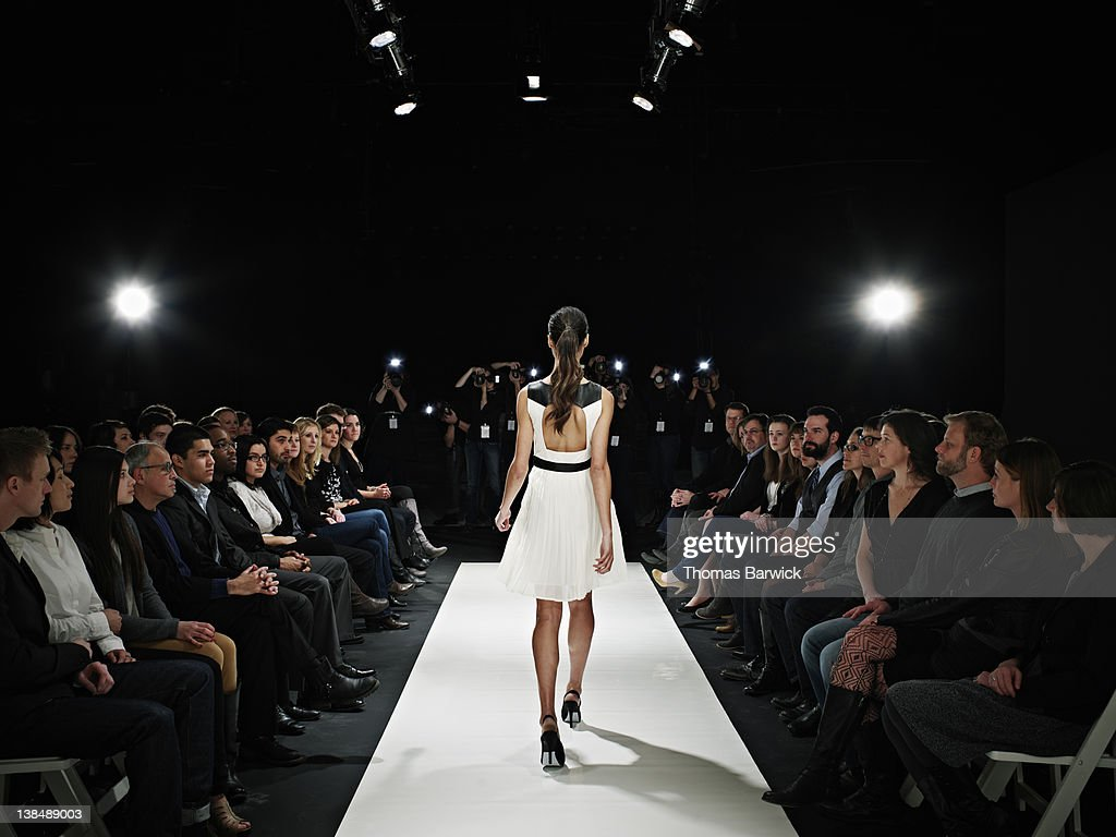 Model walking down catwalk during fashion show : Stock Photo