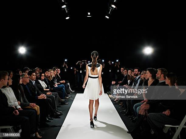 Model walking down catwalk during fashion show
