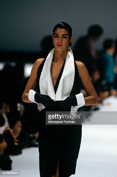 'A model walking down the catwalk with a refined black and white dress by Gianfranco Ferr Milan 1986 '