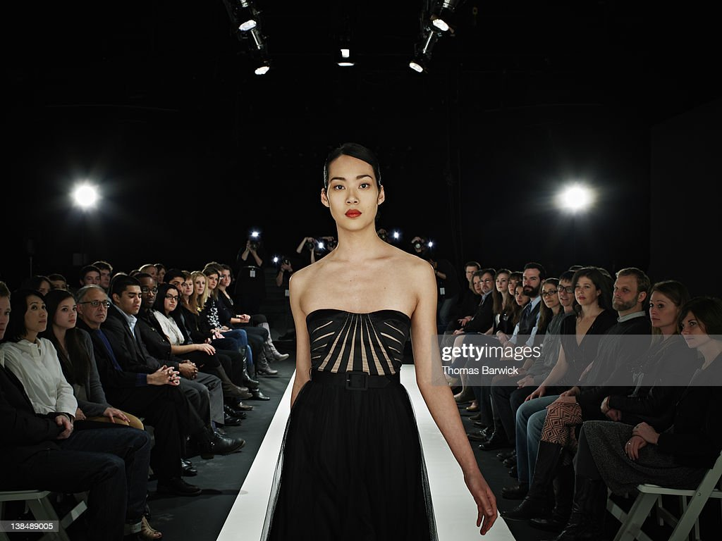 Model walking in foreground on catwalk : Stock Photo