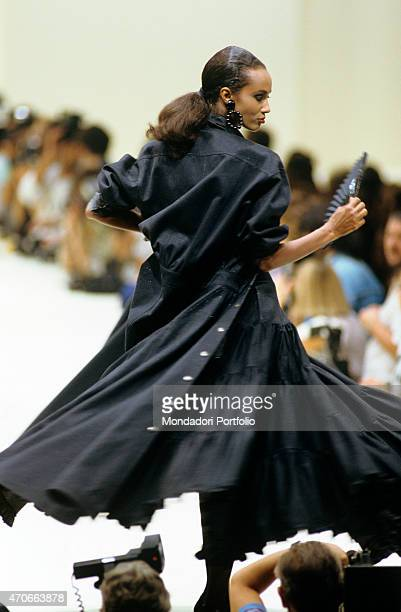 """Model walks down the catwalk, surrounded by photographers, wearing a filmy skirt and a long black coat by Fendi. Milan , 1986. """""""
