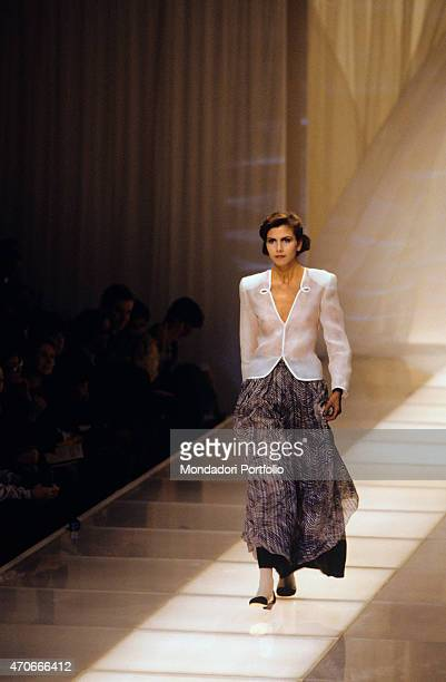 A model walks down the catwalk wearing a long dark skirt and a white blouse all by Armani Milan 1986