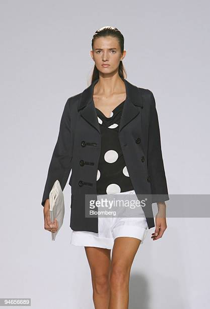 A model walks down the catwalk wearing a navy double breasted peacoat over a super dot print top with a white 2pleat short and carrying an ecru soft...
