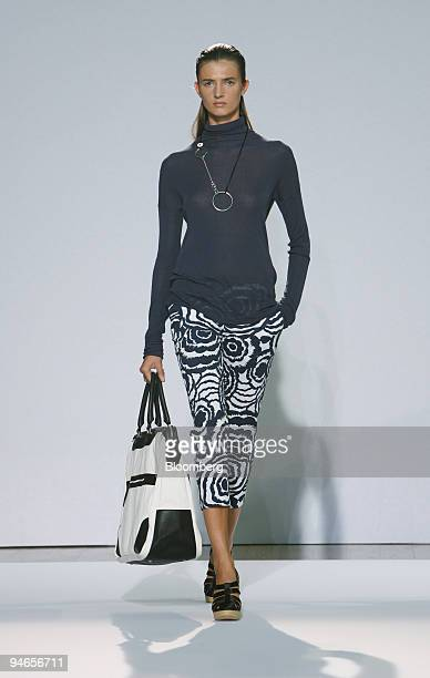 A model walks down the catwalk wearing a navy ribbed viscose roll neck over a navy rosette print cropped trouser and carrying black and white canvas...
