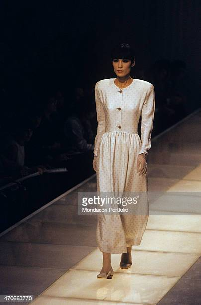 A model walks down the catwalk with a long light dress by Armani Milan 1986