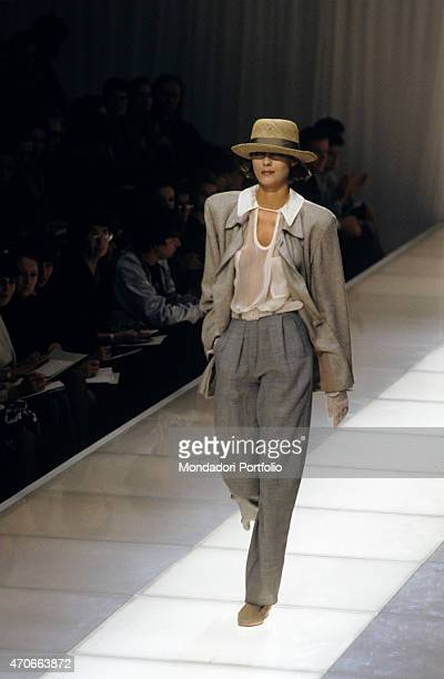 A model walks down the catwalk with a refined suit composed of jacket and trousers in the unmistakable Armani style and with a straw hat on her head...
