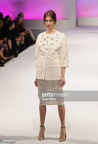 A model walks down the runway during Elyse Walker Presents The Pink Party 2013 hosted by Anne Hathaway at Barker Hangar on October 19 2013 in Santa...