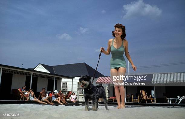 A model walks her dog in the sand wearing a 1949 blue swim suit