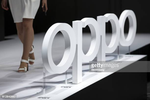 A model walks near an Oppo logo during a launch event of the company's R11s smartphone for the Japanese market in Tokyo Japan on Wednesday Jan 31...