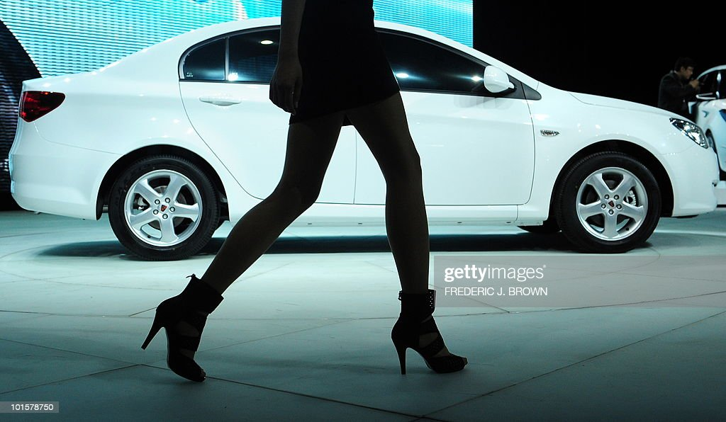 A model walks past a Roewe 350 3G during a media preview at the Beiijng Auto Show on April 23, 2010. Auto sales in booming China hit 13.64 million in 2009, overtaking the United States, as increasingly well-off Chinese consumers continued to snap up cars, helped by government incentives such as lower taxes. AFP PHOTO/Frederic J. BROWN