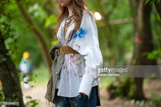 Model walks the runway and wears a gold metal large pendant necklace, a white with multicolored paint pattern oversized shirt, a brown leather belt,...