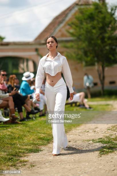 Model walks the runway and wears a white crop-top shirt, white V-belt large pants, brown shiny leather strappy pumps heels shoes / sandals, during...