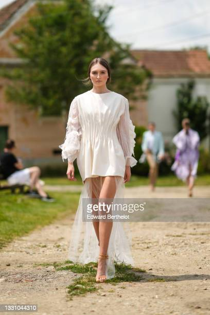 Model walks the runway and wears a white latte short ruffled dress with puffy tulle / ruffled long sleeves dress and with a long tulle train, brown...