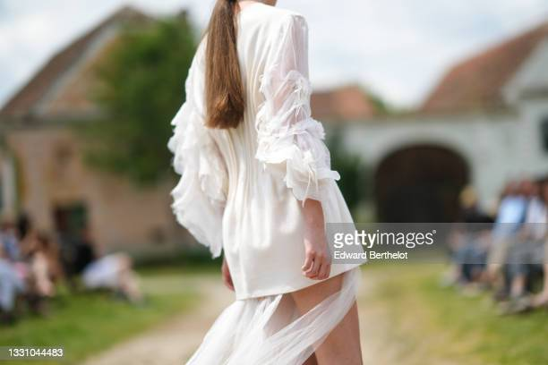 Model walks the runway and wears a white latte short ruffled dress with puffy tulle / ruffled long sleeves dress and with a long tulle train, during...