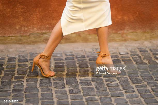 """Model walks the runway and wears a white long tube dress, brown leather strappy heels sandals / shoes, during the Ramelle show, during """"Feeric""""..."""