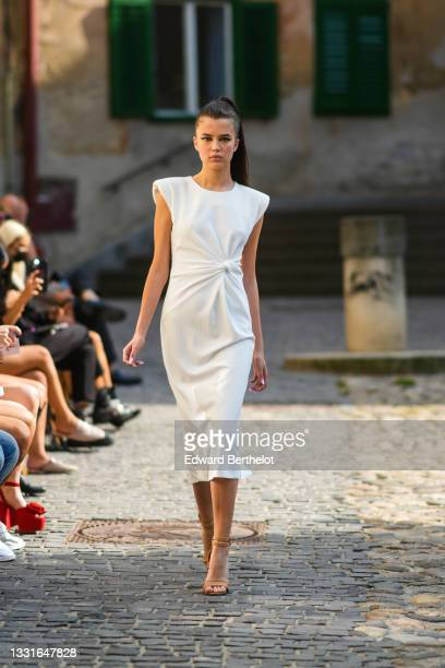 Model walks the runway and wears a white long tube knotted ribbed dress with shoulder pads, brown leather strappy heels sandals / shoes, during the...