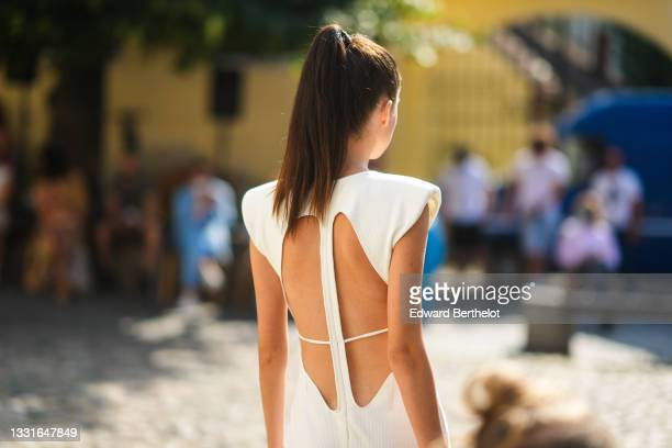 """Model walks the runway and wears a white long tube knotted ribbed dress with shoulder pads and cut-out back, during the Ramelle show, during """"Feeric""""..."""