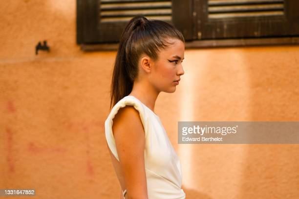 """Model walks the runway and wears a white long tube knotted ribbed dress with shoulder pads cut-out back, during the Ramelle show, during """"Feeric""""..."""