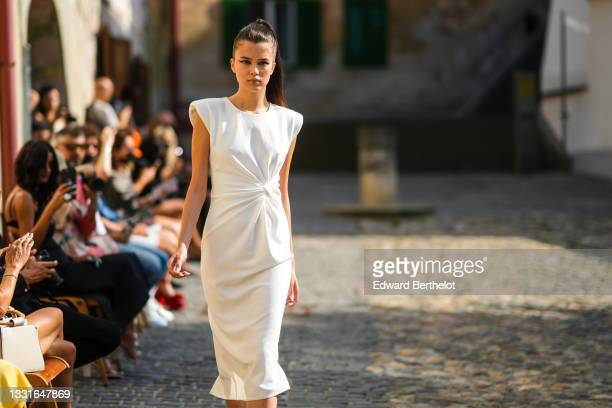"""Model walks the runway and wears a white long tube knotted ribbed dress with shoulder pads, during the Ramelle show, during """"Feeric"""" Fashion Week..."""