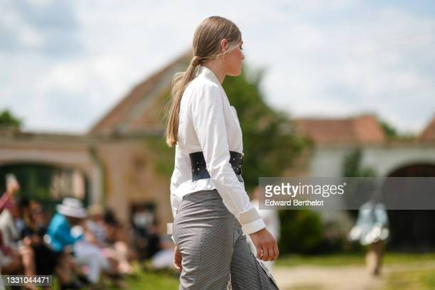 Model walks the runway and wears a white shirt, a black shiny leather large cut-put belt, black and gray checkered pattern flowing flared pants with...
