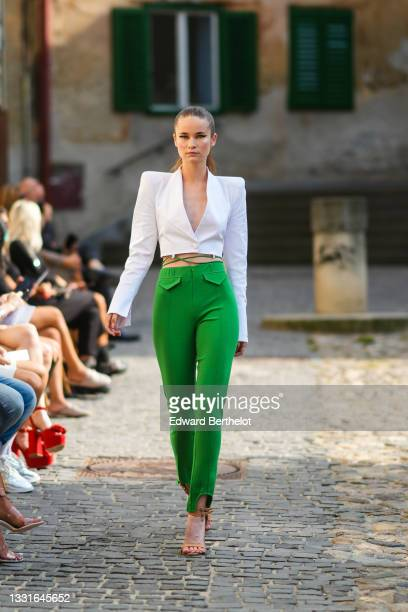 Model walks the runway and wears a white shoulder pads / V-neck / cropped blazer jacket, green laces high waist ribbed pants, black leather strappy...