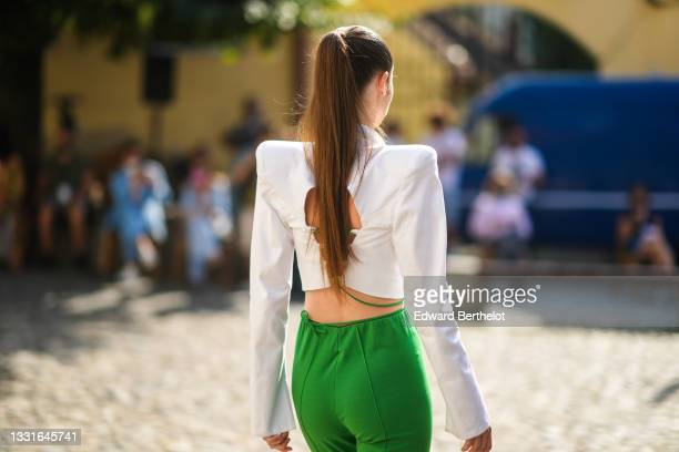 Model walks the runway and wears a white shoulder pads / V-neck / cropped blazer jacket, green laces high waist ribbed pants, during the Ramelle...