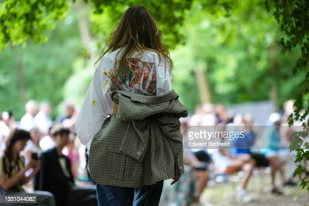 Model walks the runway and wears a white with multicolored paint pattern oversized shirt, a brown leather belt, a black and gray houndstooth print...