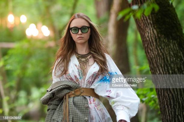 Model walks the runway and wears black sunglasses, a gold metal large pendant necklace, a white with multicolored paint pattern oversized shirt, a...