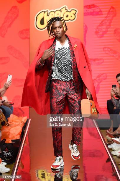 A model walks the runway as Cheetos unveiled faninspired versions of the #CheetosFlaminHaute look at The House Of Flamin' Haute Runway Show Style Bar...