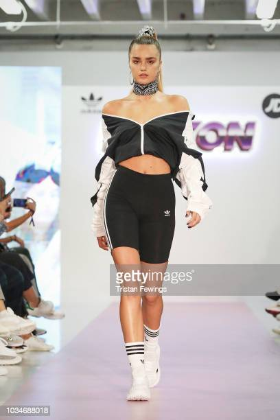 A model walks the runway at a fun and fearless 90s themed fashion show during the launch of the Icy Pink adidas Falcon at JD on September 17 2018 in...