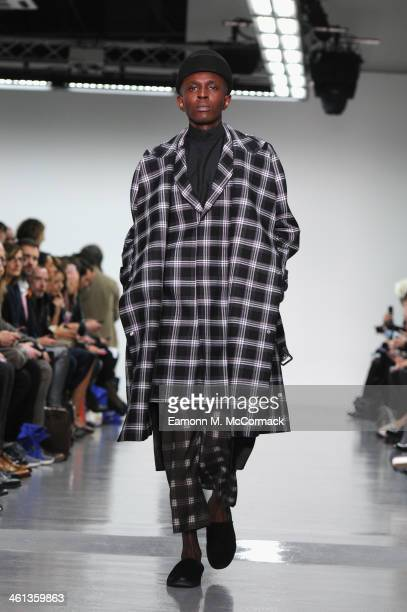 A model walks the runway at the Agi Sam show during The London Collections Men Autumn/Winter 2014 on January 8 2014 in London England