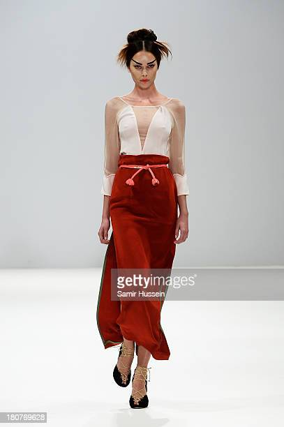 A model walks the runway at the Ji Cheng Sheme show during at the Fashion Scout venue during London Fashion Week SS14 at Freemasons Hall on September...