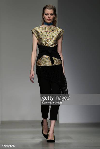 A model walks the runway at the Osman show at London Fashion Week AW14 at on February 18 2014 in London England
