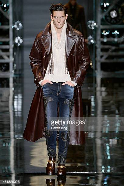 A model walks the runway at the Versace Autumn Winter 2014 fashion show during Milan Menswear Fashion Week on January 11 2014 in Milan Italy