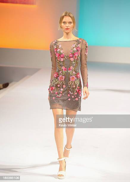A model walks the runway during Elyse Walker Presents The Pink Party 2013 hosted by Anne Hathaway at Barker Hangar on October 19 2013 in Santa Monica...