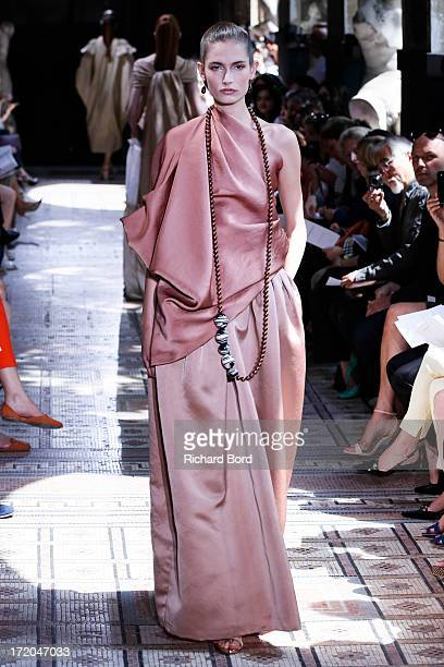 A model walks the runway during the Christophe Josse show as part of Paris Fashion Week HauteCouture Fall/Winter 20132014 at les Beaux Arts on July 1...