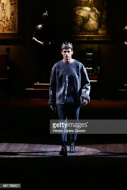 A model walks the runway during the Dolce Gabbana show as a part of Milan Fashion Week Menswear Autumn/Winter 2014 on January 11 2014 in Milan Italy