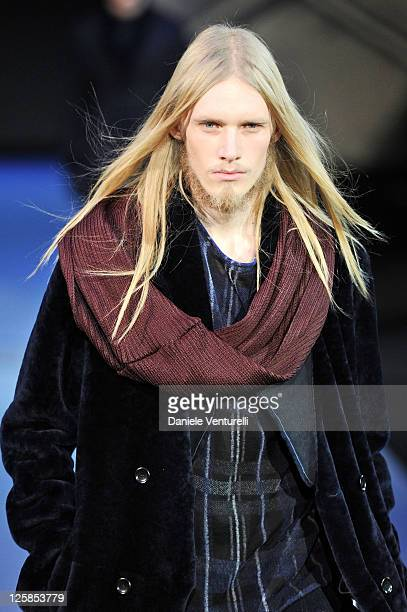 Model walks the runway during the Emporio Armani fashion show as part of Milan Fashion Week Menswear A/W 2011 on January 16, 2011 in Milan, Italy.