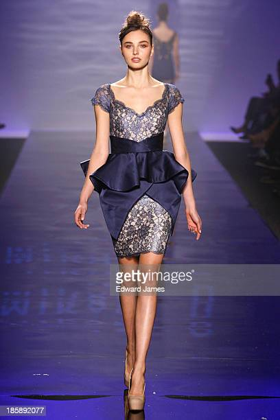 A model walks the runway during the Mikael D fashion show during 2013 Toronto Fashion Week at David Pecaut Square on October 25 2013 in Toronto Canada