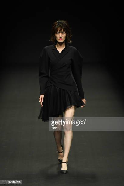 A model walks the runway during the YOUG X collection show by Chinese designer Xing Yong on day three of China Fashion Week at 751DPARK on October 26...