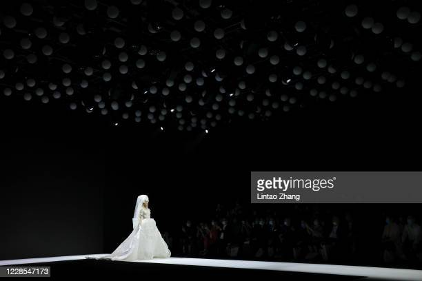 Model walks the runway for a collection show by Chinese designer Laurence Xu during the day two of Beijing Fashion Week at Wangfujing street on...