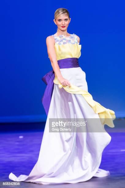 A model walks the runway wearing a Benito Santos design at the Metropolitan Fashion Week Closing Night Gala at Arcadia Performing Arts Center on...