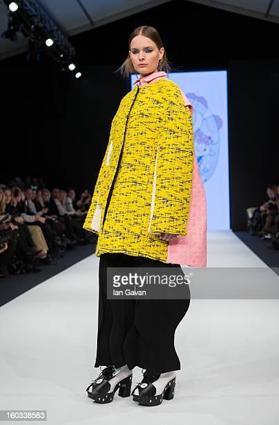 A model walks the runway wearing designs by winner Minju Kim during the HM Design Award at MercedesBenz Stockholm Fashion Week Autumn/Winter 2013 at...
