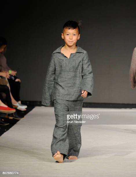 A model walks the runway wearing Plaid Paisley Little at 2017 Vancouver Fashion Week Day 6 on September 23 2017 in Vancouver Canada