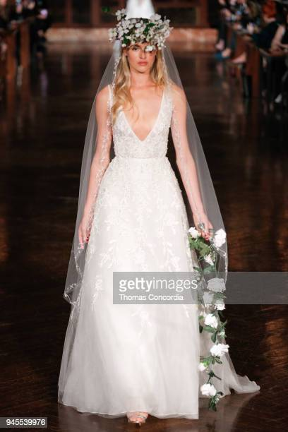 A model walks the runway wearing Reem Acra Spring 2019 Bridal Collection with hair by Brian Buenaventura and makeup by Cassandra Garcia at the New...
